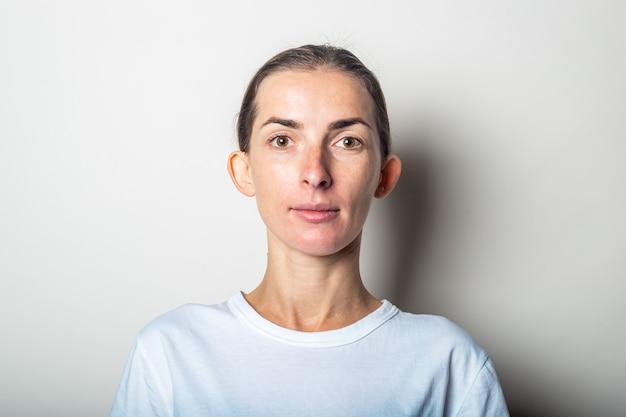 Jonge vrouw met uitstekende oren, op een lichte muur