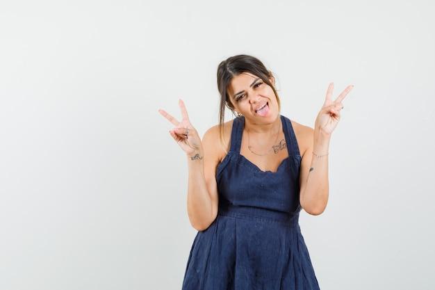 Jonge vrouw met v-sign, tong uitsteekt in jurk en op zoek gek