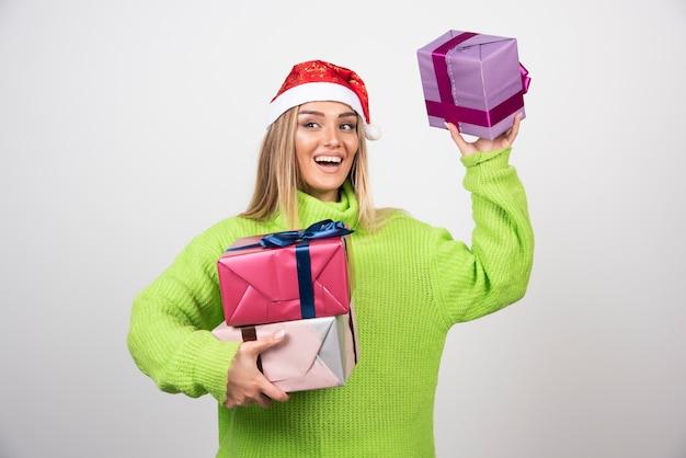Jonge vrouw met veel feestelijke kerstcadeautjes.