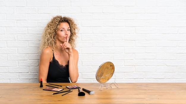 Jonge vrouw met veel make-upborstel in een lijst die stiltegebaar doet