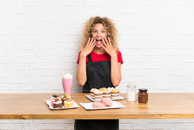 Jonge vrouw met veel verschillende minicakes in een lijst met verrassingsgelaatsuitdrukking