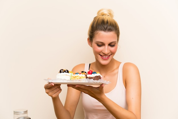 Jonge vrouw met veel verschillende minicakes in een lijst