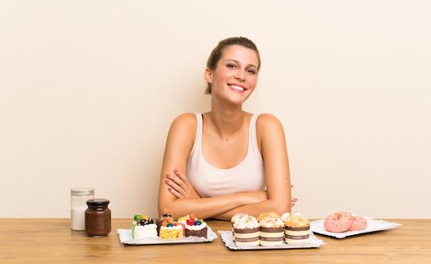 Jonge vrouw met veel verschillende minicakes in lijst het lachen