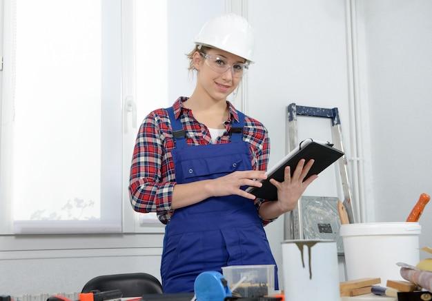 Jonge vrouw met veiligheidshelm, met behulp van een digitale tablet