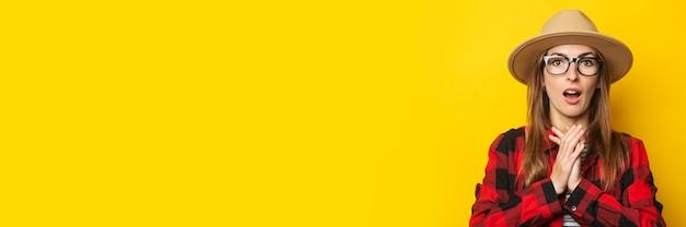Jonge vrouw met verbaasd gezicht in hoed en plaidoverhemd op geel.