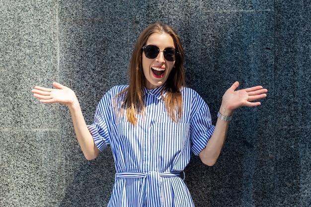 Jonge vrouw met verbaasd gezicht in jurk en bril op de achtergrond van een stenen muur.