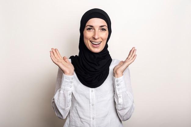 Jonge vrouw met verbaasd gezicht in wit overhemd en hijab