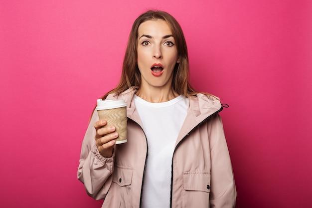 Jonge vrouw met verbaasd gezicht met papieren beker met koffie in de hand op roze oppervlak