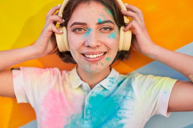 Jonge vrouw met verf op gezicht en koptelefoon