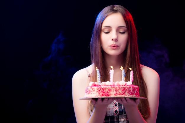 Jonge vrouw met verjaardagscake op feestje