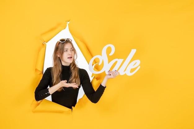 Jonge vrouw met verkoop schrijven door gescheurd papier gat in de muur