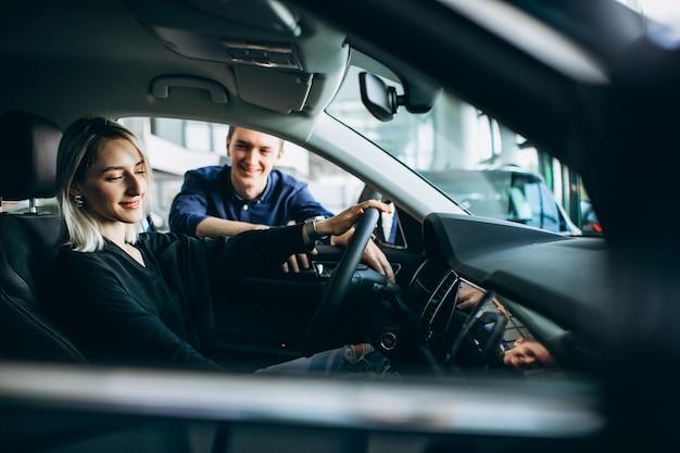 Jonge vrouw met verkoper bij een carshowroom