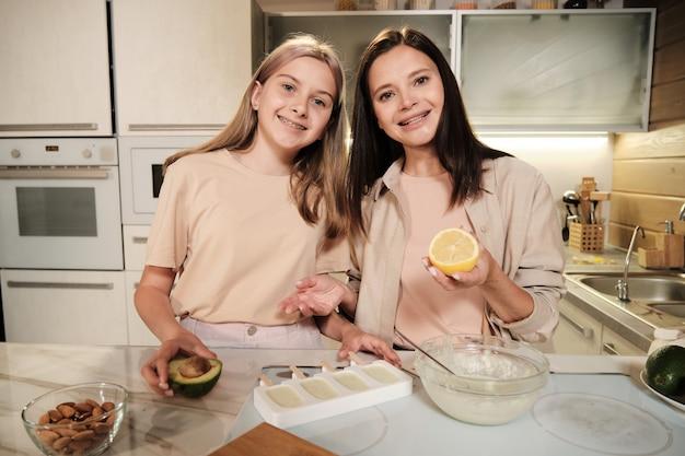 Jonge vrouw met verse citroen en haar dochter met avocado kijken naar je terwijl ze uitleggen hoe ze zelfgemaakt ijs kunnen bereiden