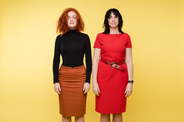 Jonge vrouw met verwarde haren poseren na conflict geïsoleerd op gele studio achtergrond. twee mode-vriendinnen of stijlvolle zakenvrouwen met positieve emotie