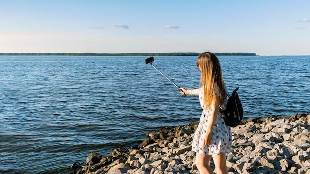 Jonge vrouw met video-oproep met behulp van smartphone en monopod tegen de achtergrond van het reservoir