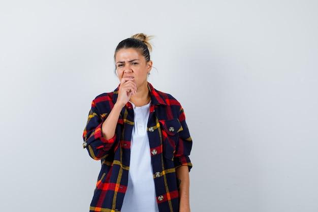 Jonge vrouw met vinger in mond in geruit overhemd en verbaasd, vooraanzicht.