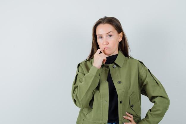 Jonge vrouw met vinger op haar mond in groene jas en op zoek verward, vooraanzicht.