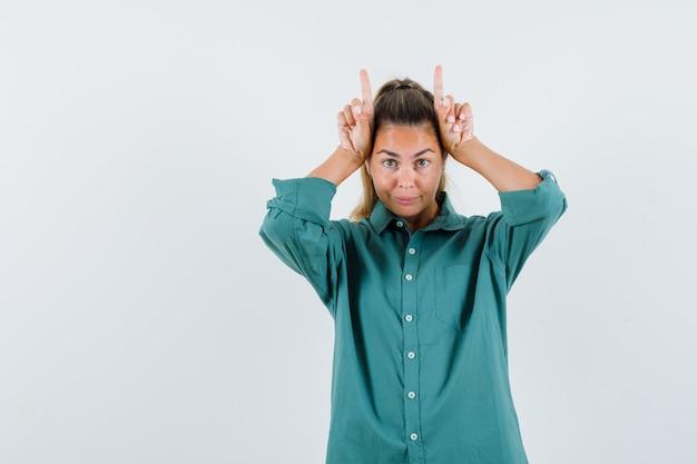 Jonge vrouw met vingers boven het hoofd als stier hoorns in groene blouse en schattig kijken