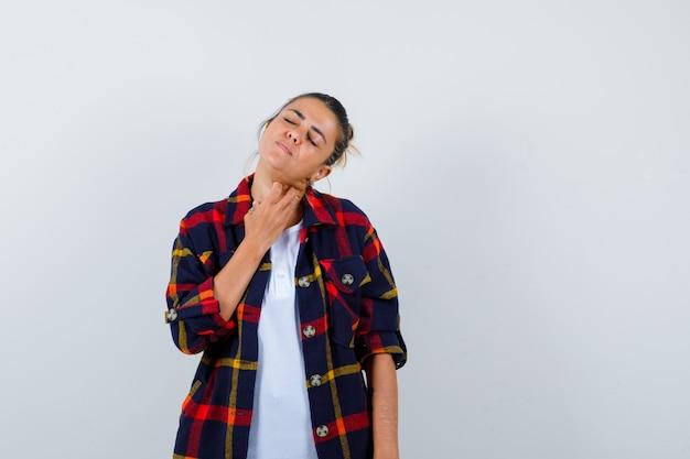 Jonge vrouw met vingers op nek in geruit overhemd en pijnlijk, vooraanzicht.