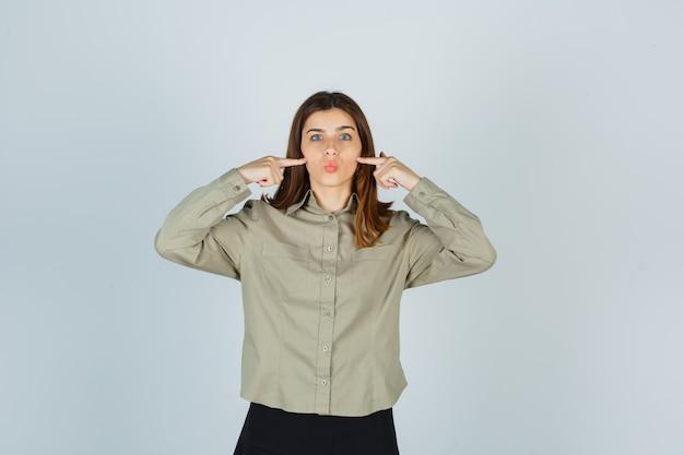 Jonge vrouw met vingers op wangen, lippen gevouwen in shirt te houden