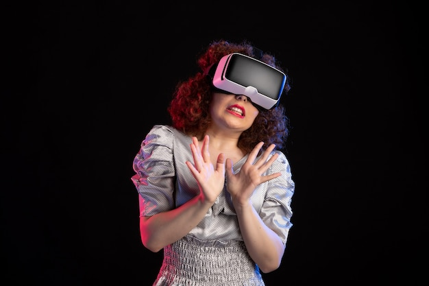 Jonge vrouw met virtual reality headset op donkere ondergrond