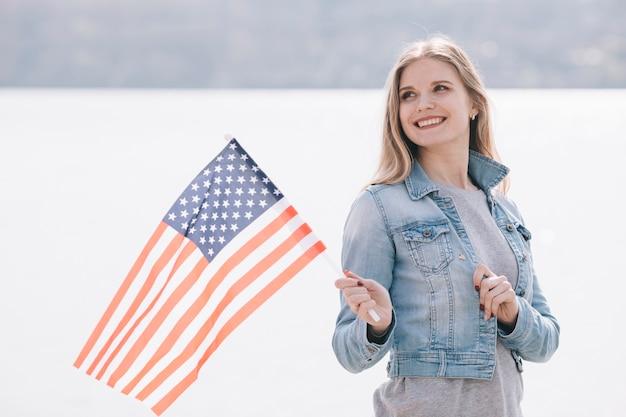 Jonge vrouw met vlag van de vs zwaaien