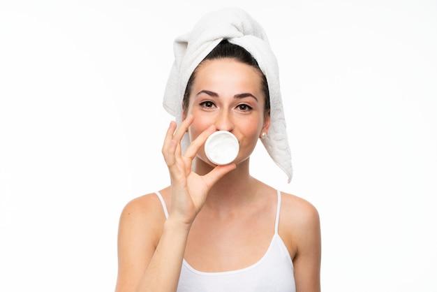 Jonge vrouw met vochtinbrengende crème over geïsoleerde witte muur