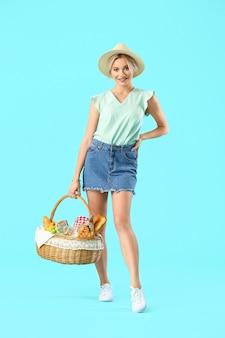 Jonge vrouw met voedsel voor picknick in mand op gekleurde achtergrond