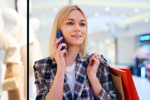 Jonge vrouw met volle boodschappentassen praten via mobiele telefoon