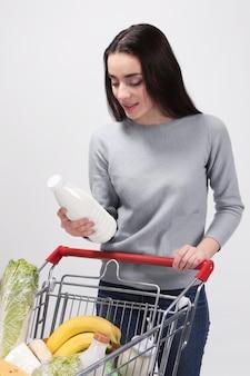 Jonge vrouw met volledige het winkelen handkar op licht