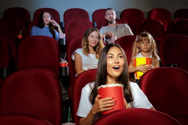 Jonge vrouw met vrienden die op film in bioskoop letten