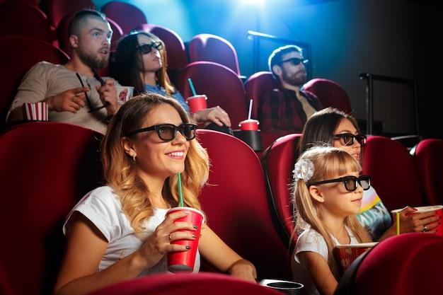 Jonge vrouw met vrienden kijken naar film in de bioscoop