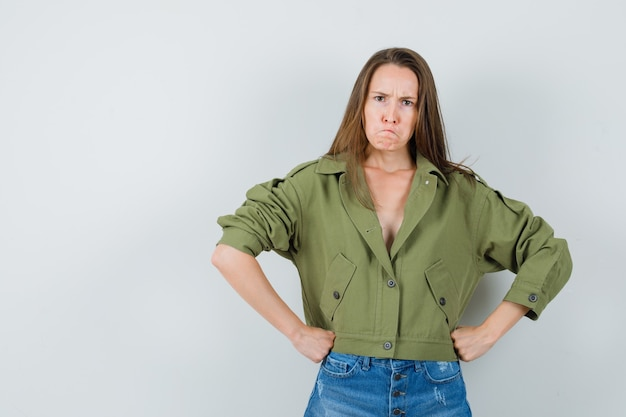 Jonge vrouw met vuisten op taille in groene jas, korte broek en nerveus op zoek. vooraanzicht.