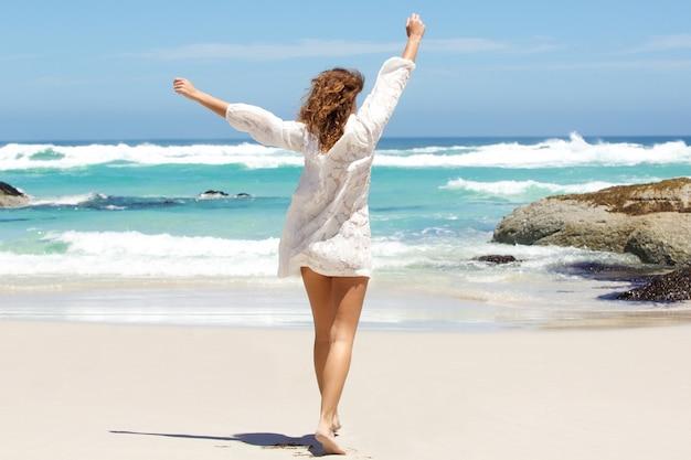 Jonge vrouw met wapens die in de lucht op het strand worden opgeheven