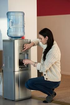 Jonge vrouw met water dispenser op kantoor