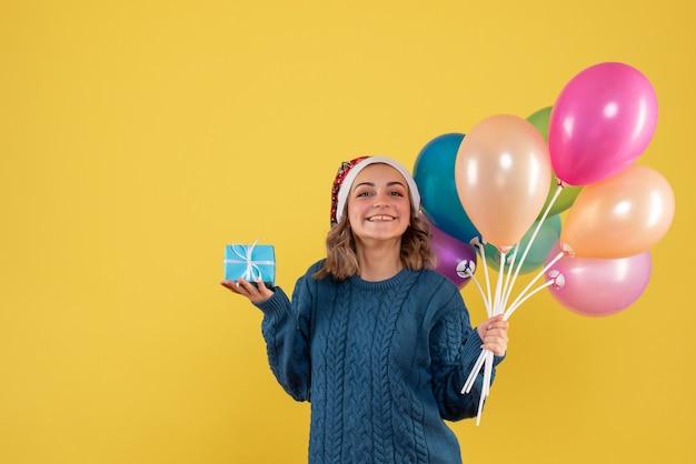 Jonge vrouw met weinig aanwezig en ballonnen op geel