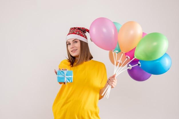 Jonge vrouw met weinig aanwezig en kleurrijke ballonnen op wit