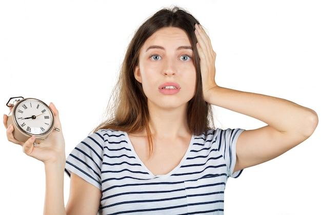 Jonge vrouw met wekker die op wit wordt geïsoleerd. tijd management concept