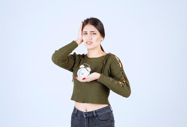 Jonge vrouw met wekker met hoofdpijn op witte achtergrond.