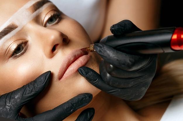 Jonge vrouw met wenkbrauwmarkering met permanente make-up op lippen in schoonheidssalon