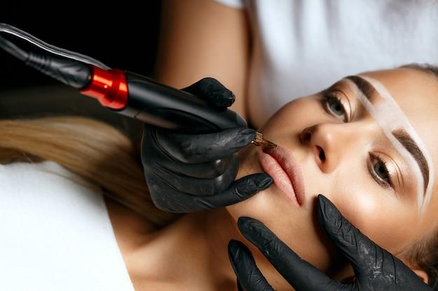 Jonge vrouw met wenkbrauwpasta op haar wenkbrauwen met permanente make-up op lippen in schoonheidssalon