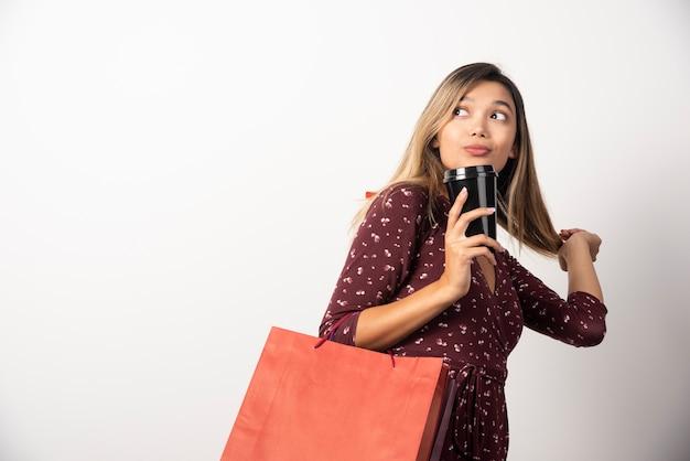 Jonge vrouw met winkel tassen en een kopje drank op witte muur.