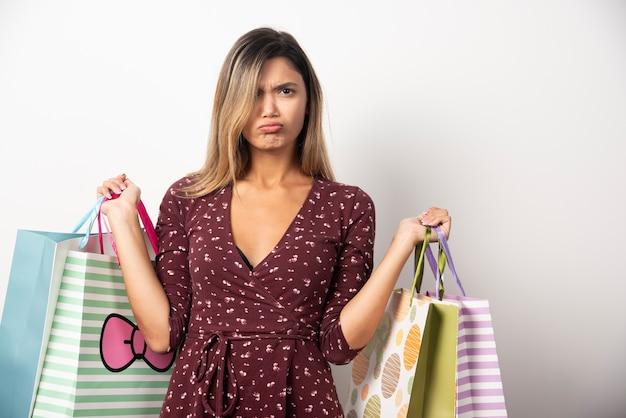 Jonge vrouw met winkeltassen op witte muur.