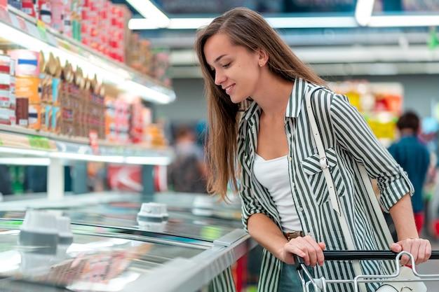 Jonge vrouw met winkelwagen kiest producten bij de supermarkt. supermarkt eten