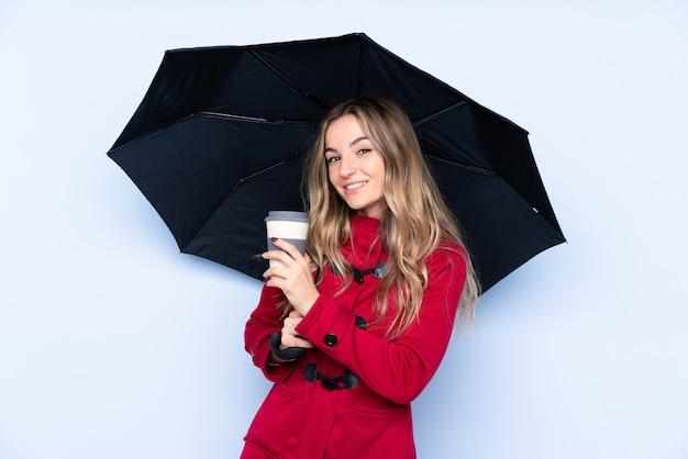Jonge vrouw met winterjas met een paraplu en een koffie om mee te nemen