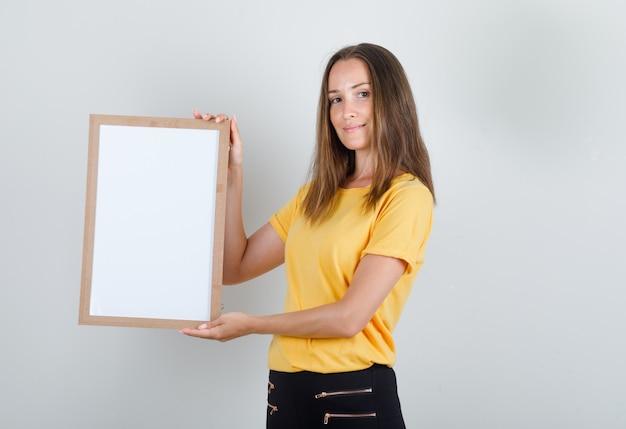 Jonge vrouw met wit bord en lachend in geel t-shirt