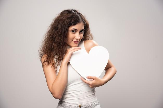 Jonge vrouw met wit handgeschept papier hart. hoge kwaliteit foto