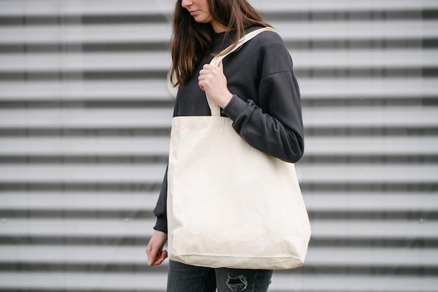 Jonge vrouw met witte eco textielzak tegen stedelijke stad