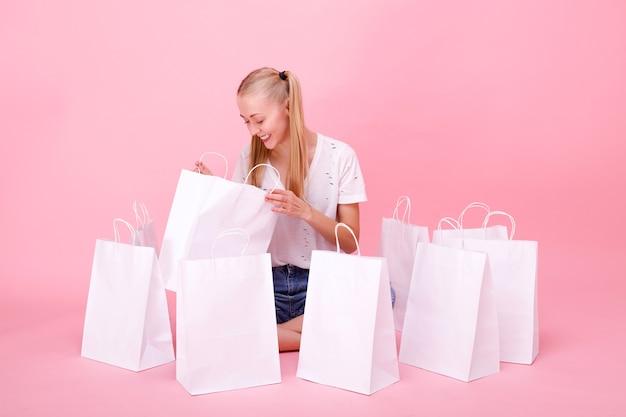 Jonge vrouw met witte papieren zakken op roze