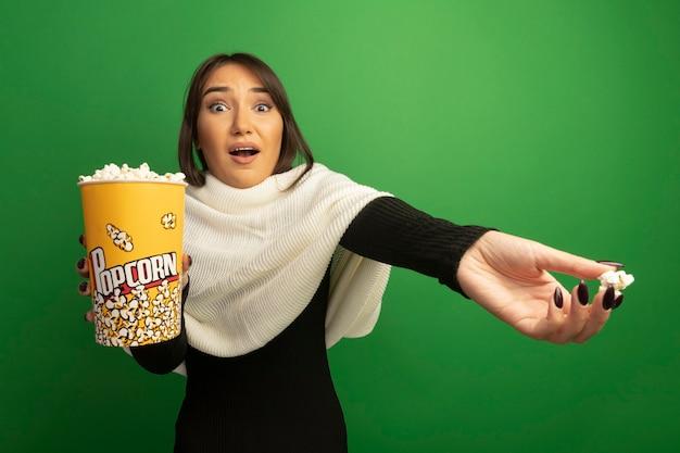 Jonge vrouw met witte sjaal die emmer met popcorn toont die met uit wapen wordt verward